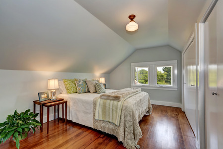 attic: Attic bedroom interior with vaulted ceiling and hardwood floor. Nice bed cover and colorful pillows.  Northwest, USA
