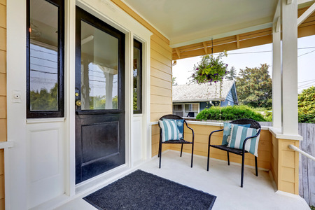 home exterior: Covered porch with black front door and two wicker chairs with striped pillows . Northwest, USA Stock Photo