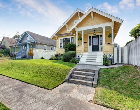 home exterior: American craftsman home with yellow exterior paint and well kept front garden. Northwest, USA Stock Photo