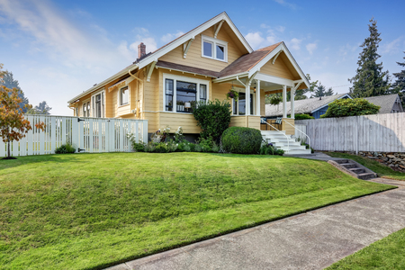kept: American craftsman home with yellow exterior paint and well kept front garden. Northwest, USA Stock Photo