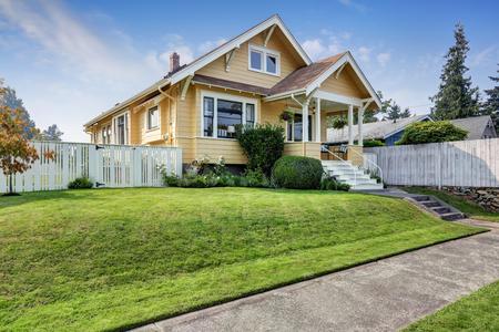 artesano: casa artesano americano con pintura exterior de color amarillo y jardín delantero bien cuidado. Noroeste, EE.UU.