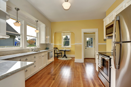 Kitchen interior with white cabinets, stainless steel appliances, yellow walls and hardwood floor. Northwest, USA
