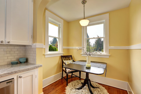yellow walls: Small dining room area with yellow walls. Compact size table with one chair on a Round soft shaggy carpet. Northwest, USA