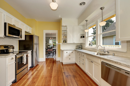 yellow walls: Kitchen interior with white cabinets, stainless steel appliances, yellow walls and hardwood floor. Northwest, USA