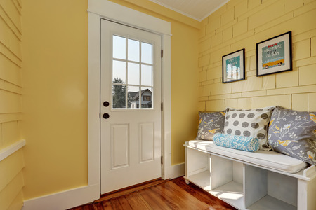 Entryway with yellow walls and storage bench in white with colorful pillows.Northwest, USA Foto de archivo