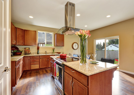 range hood: Traditional American kitchen featuring stainless steel appliances, range hood, an island and granite countertops. Northwest, USA Stock Photo
