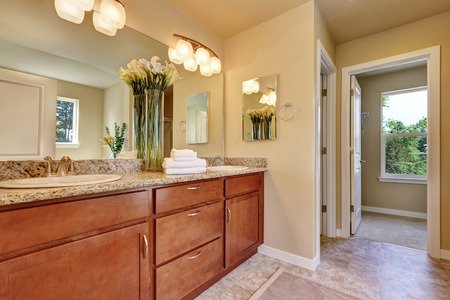 countertops: Photo of a mid-sized bathroom with wood cabinets, granite countertops and beige walls. Decorated with fresh flowers. Northwest, USA