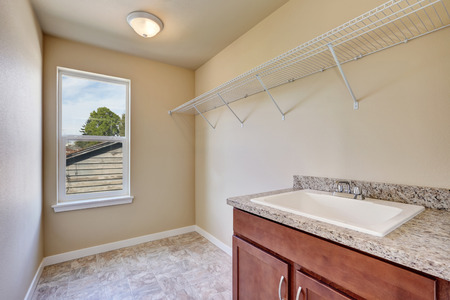laundry room: Empty laundry room interior upstairs with tile floor an beige walls. Northwest, USA