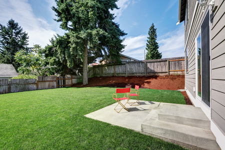 northwest: Fenced backyard garden filled with green grass and furnished with two red chairs. Northwest, USA