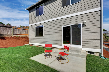 fenced: Fenced backyard garden filled with green grass and furnished with two red chairs. Northwest, USA