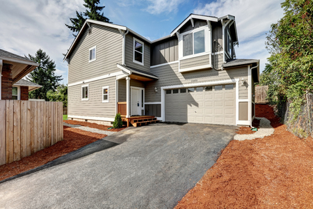 garage on house: American gray house exterior with garage and driveway. Northwest, USA Stock Photo