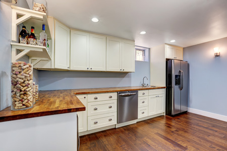Lavender Kitchen room in the basement of craftsman house. Built-in stainless steel fridge, wooden counter top and white cabinets. Northwest, USA Stock Photo