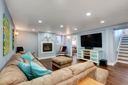 Pastel blue walls in basement living room interior. Large corner sofa with blue pillows and ottoman. Vintage white and blue TV cabinet. Northwest, USA