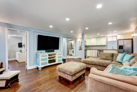 Pastel blue walls in basement living room interior with open floor plan. Large corner sofa with blue pillows and ottoman. Vintage white and blue TV cabinet. Northwest, USA Foto de archivo