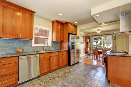 タイル張りの床とモダンな黒いキャビネット キッチン インテリア モザイク緑の backsplash およびステンレス鋼の電気器具です。米国北西部 写真素材