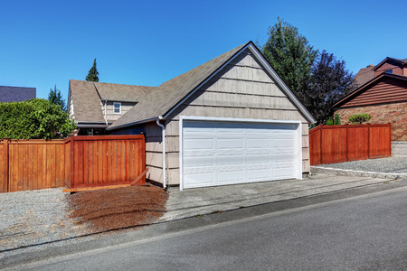 garage on house: White door garage and fenced back yard of American craftsman house. Northwest, USA.