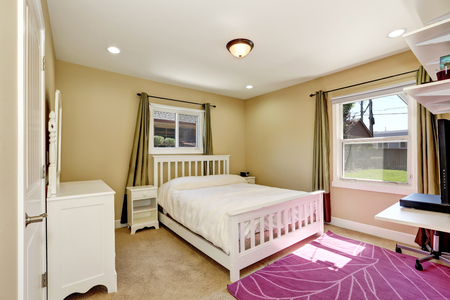 home accent: Nicely furnished bedroom in small American craftsman style home. Accent color home design. Green olive window curtains and purple rug. Northwest, USA