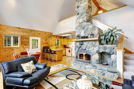 inter Maison avec plafond voûté et plan d'étage ouvert. Séjour avec cheminée en pierre et vue sur la cuisine en bois. Northwest, États-Unis