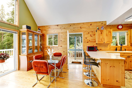 House interior with vaulted ceiling and open floor plan.  Dining room and kitchen room with wooden wall paneling. Northwest, USA