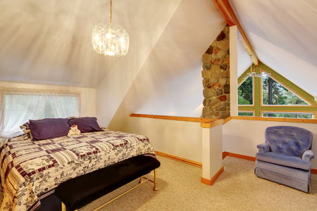 upstairs: Vaulted ceiling bedroom interior upstairs. Nice bed with bench and carpet floor. Northwest, USA Stock Photo