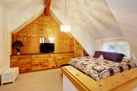 Vaulted ceiling bedroom with wooden paneled wall and cabinet with drawers. Northwest, USA