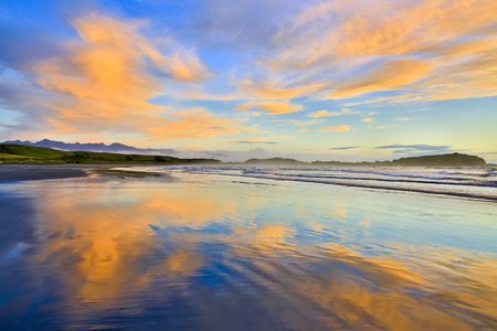 sky reflection: View of Sandy beach at Sunset with sky reflection in the water. Westport of New Zealand.
