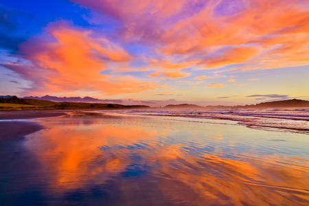 erode: Sandy beach and orange clouds at the sunset in Westport, New Zealand