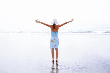 Happy woman silhouette raising her hands, appreciating beautiful landscape. Westport, New Zealand. Stock Photo