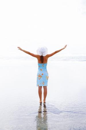appreciating: Happy woman silhouette raising her hands up, appreciating beautiful landscape. Westport, New Zealand.