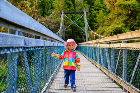Little girl in bright colorful coat walks on the bridge. Haast, New Zealand