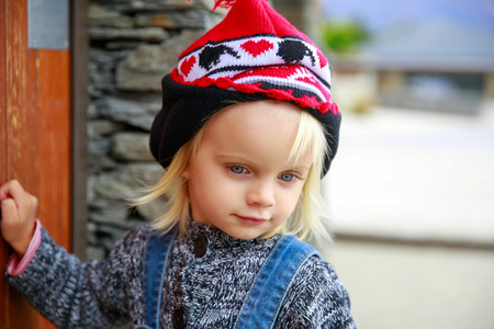 knocking: Phote of a Cute little girl with blue eyes knocking at the door. Lake Wanaka town, New Zealand Stock Photo