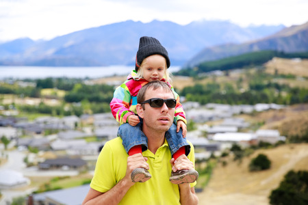 outside house: Young man in sunglasses with a little girl on his shoulders. At the back  Lake Wanaka town, New Zealand Stock Photo