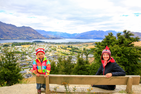 Pretty young woman with her daughter are sitting on the bench of the mountain top with Panoramic view of lake Wanaka town at the back.  New Zealand