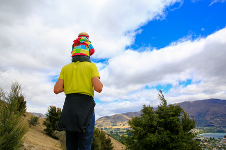 Young man with a little girl on his shoulders staying on the top of the mountain and appreciating beautiful lake Wanaka landscape, New Zealand Banco de Imagens