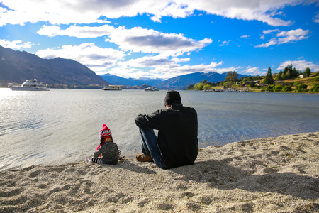 Father with little daughter sitting on sandy beach, appreciating Lake Wanaka landscape in Otago region, South Island, New Zealand
