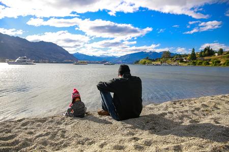 appreciating: Father with little daughter sitting on sandy beach, appreciating Lake Wanaka landscape in Otago region, South Island, New Zealand