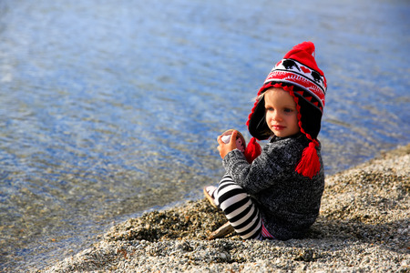 lake beach: Little girl is sitting on sandy beach and trying to take the shues off. Lake Wanaka, New Zealand Stock Photo