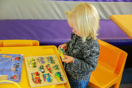 puzzling: Wanaka, New Zealand - Febr 5, 2015: cute little girl sitting at the table and playing wooden puzzle. Cafe interior background, Puzzling world.