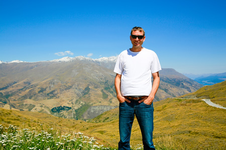 Young man in sunglasses standing on the top of the Mount. Mt Aspiring landscape in Wanaka, New Zealand