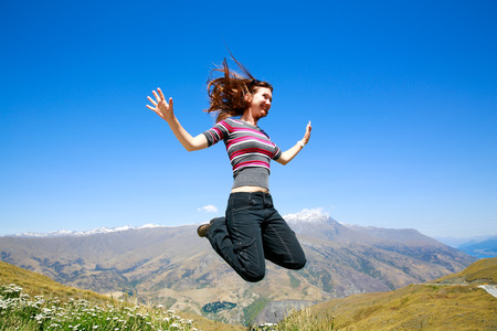 aspiring: Happy Young woman jumping with Mt Aspiring landscape view in Wanaka, New Zealand