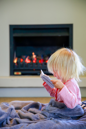 te: Cute little girl with notebook sitting under the cover and fireplace background. Te Anau. New Zealand Stock Photo