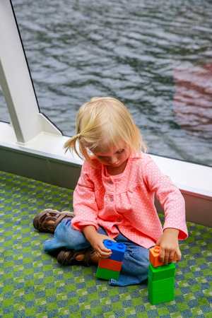 screened: Adorable kid playing with constructor on a boat, lake Te Anau, New Zealand