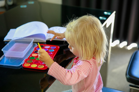 te: Adorable little girl is getting ready for painting. Te Anau, New Zealand Stock Photo