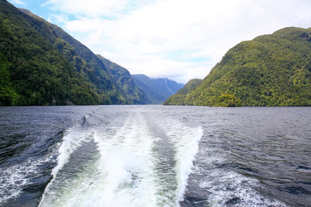 Back view of a boat, cruising on calm water and overlooking beautiful landscape. Milford Sound, New Zealand.
