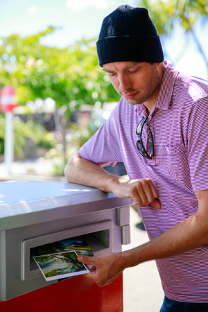 anau: Young man in a hat is taking photos from the box. Te Anau, New Zealand Stock Photo