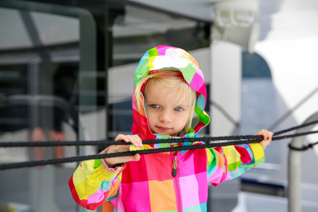 te: Adorable kid in colorful coat looking at water from the touring boat, Te Anau, New Zealand