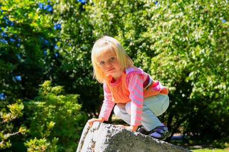 botanic: Adorable child climbing stone wall. Christchurch Botanic Garden. New Zealand Stock Photo