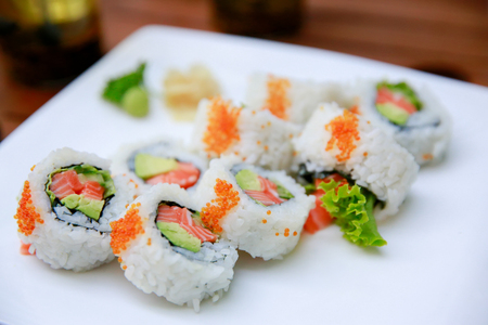 Rolls with salmon, avocado and caviar over white background.