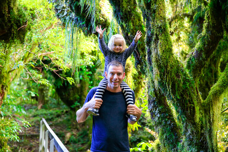 trailing: Happy young father with his daughter in Rain forest .Trailing moss and gnarled trees, Egmont National Park, Taranaki, North Island, New Zealand