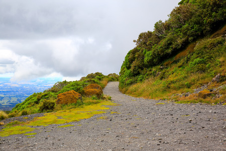 egmont: Track to Mount Taranaki on cloudy sky background. New Zealand Stock Photo